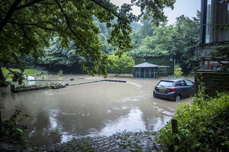 In Heerlen is een tuin ondergelopen door de zware regenval.  Beeld Marcel van Hoorn / ANP
