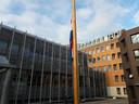 Strak hangend aan een vlaggenmast hangt de Nederlandse vlag halfstok bij de ingang van het Bossche Paleis van Justitie.