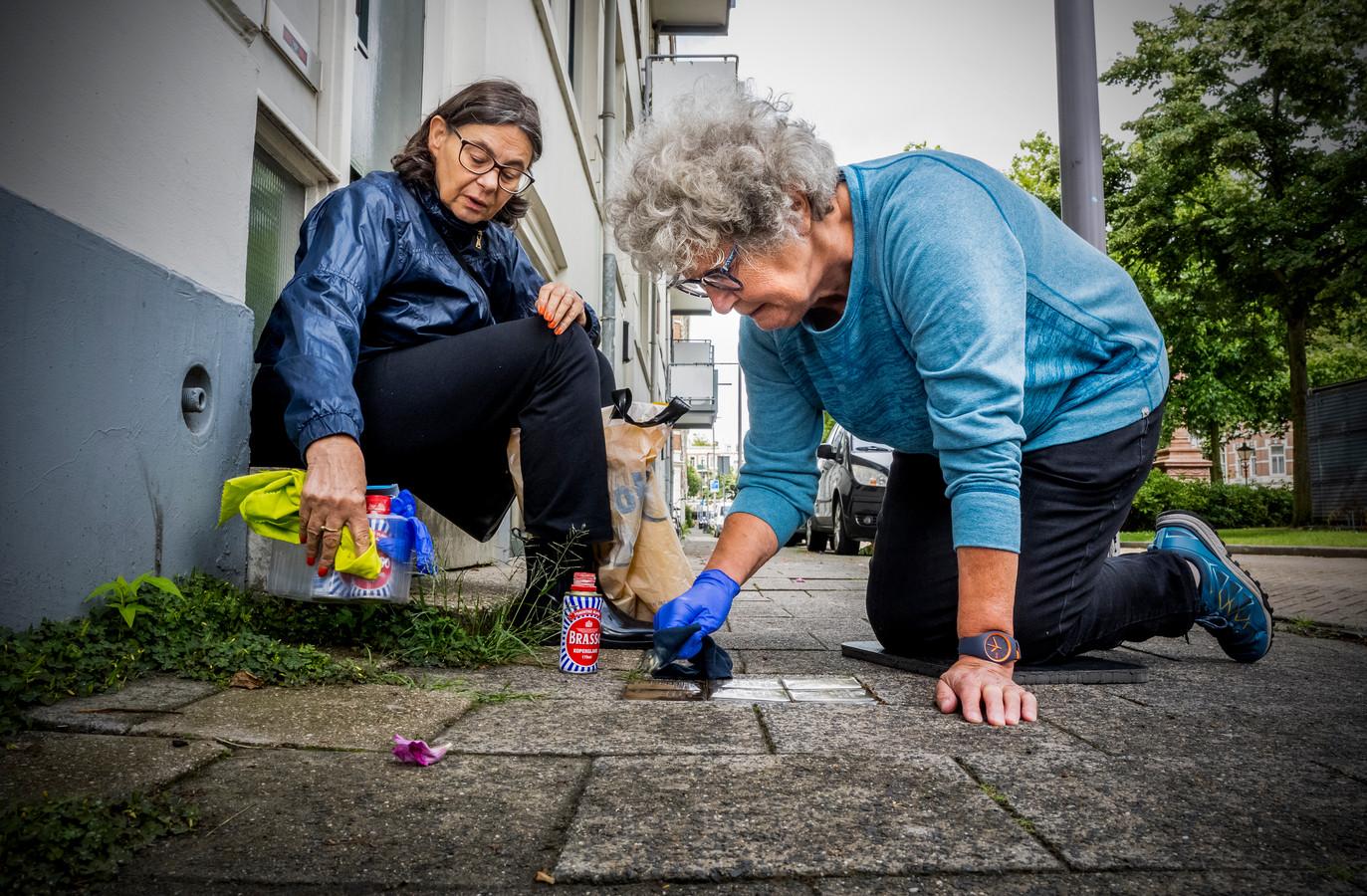 Ellen Vomberg en Rinie Hoff maken de struikelstenen op het Noordereiland schoon.