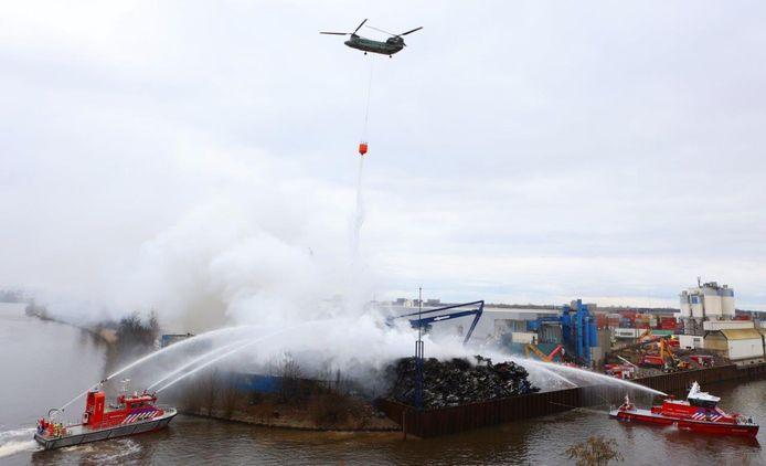 Blusboten en defensiehelikopter bezig met het blussen van de brand bij A.V.I in Den Bosch.