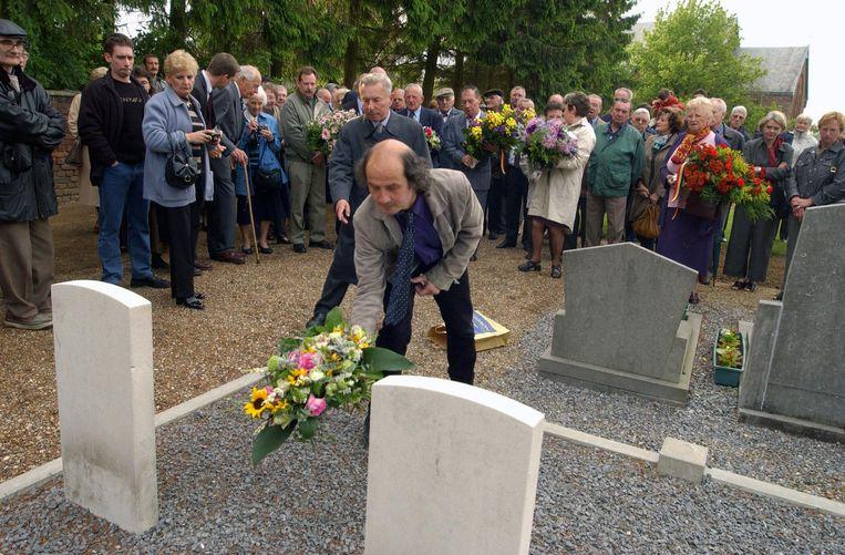Timothy Minnitt, zoon van overlevende Arthur, legt tijdens een herdenking kransen op de graven van de twee piloten, Dane en Body.
