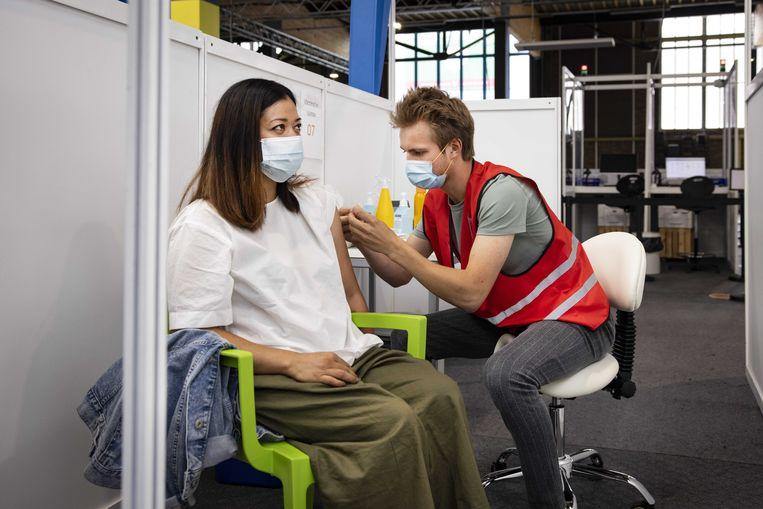 Iemand wordt gevaccineerd in de NDSM-loods in Amsterdam. Beeld ANP