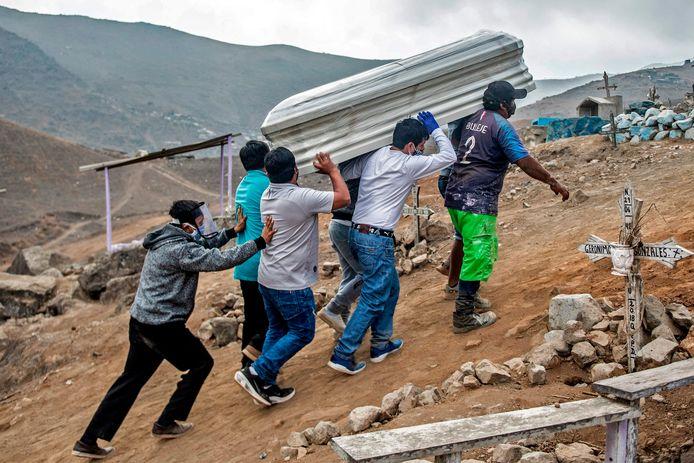 Familieleden dragen de kist van een aan corona overleden familielid naar zijn laatste rustplaats op een begraafplaats buiten Lima.