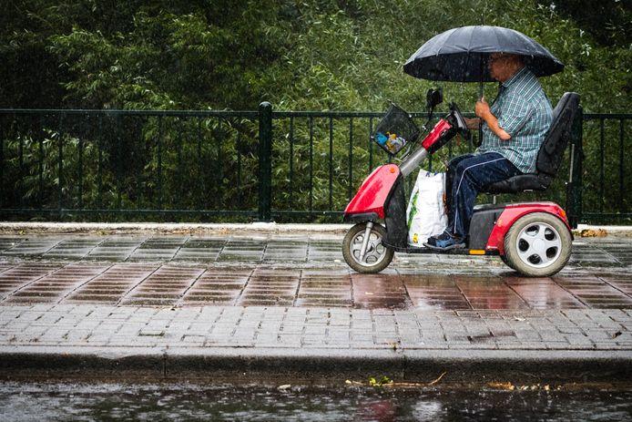 Een man in een scootmobiel met een paraplu.