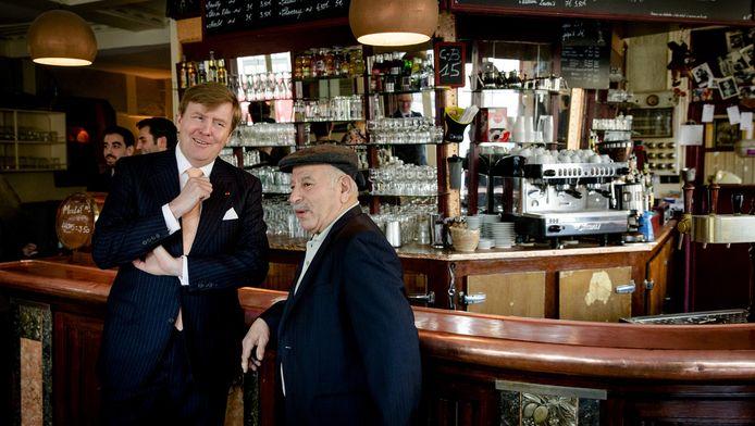 Koning Willem-Alexander in café Le Carillon. Het koningspaar sprak met de eigenaar, een medewerker, buurtbewoners en hulpverleners, die aanwezig waren tijdens of vlak na de aanslagen van 13 november 2015.