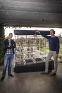 Clemens Mensink (rechts) en zijn compagnon Bart Sprenkels bij de bineaire rekenmachine die Mensink zelf in elkaar heeft gezet. Het is een voorbeeld van de technische sculpturen die Mensink wil maken via het project de creatieve broedplaats.