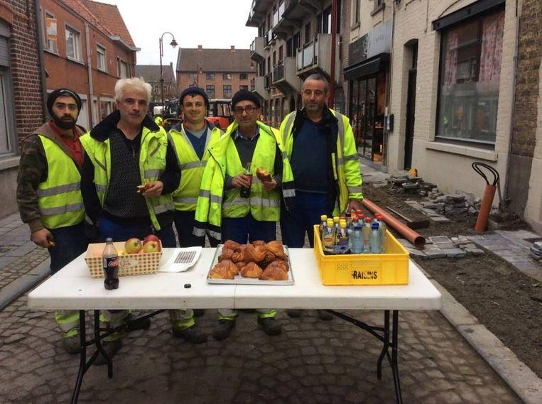 De werkmannen lieten zich de traktatie van bakker Vincent Gozin smaken.