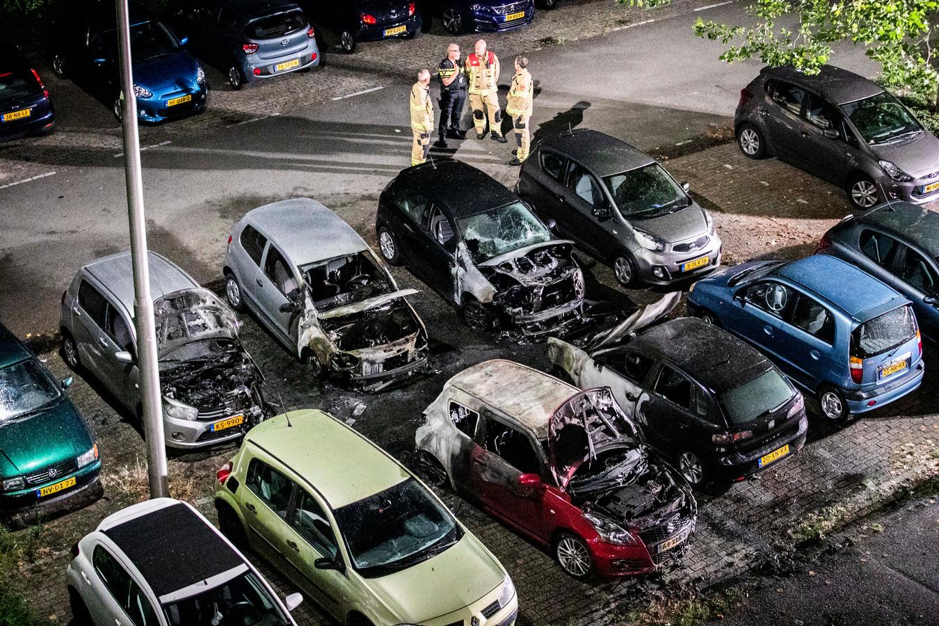 Vijf door brand verwoeste auto's op de parkeerplaats voor een flat aan de Leimuidenplaats in Arnhem-Zuid.