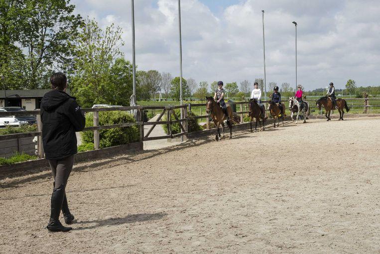 Kinderen krijgen weer paardrijles bij manege de Prinsenstad in Delft. Om verspreiding van het coronavirus te voorkomen moet ook in de manege 1,5 meter afstand worden gehouden.  Beeld ANP