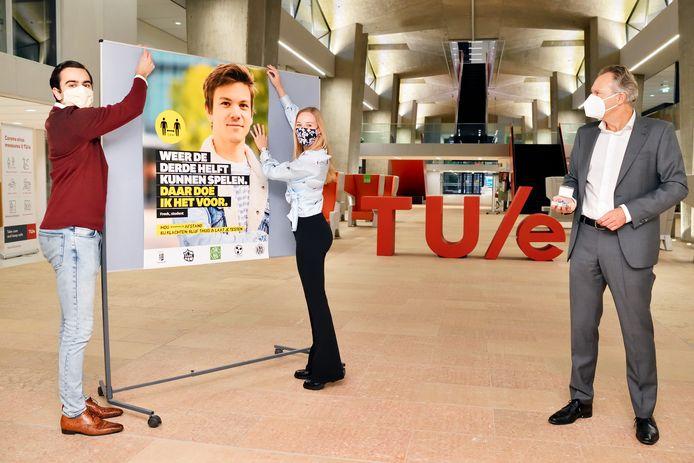 Eindhovense studenten voeren coronacampagne voor jongeren: de eerste poster wordt opgeprikt door Nikola Penev (algemene studentenverenigingen koepel Compositum) en Roxane Wijnen (studieverenigingen koepel FSE). Rechts Robert-Jan Smits, voorzitter College van bestuur van TU Eindhoven.