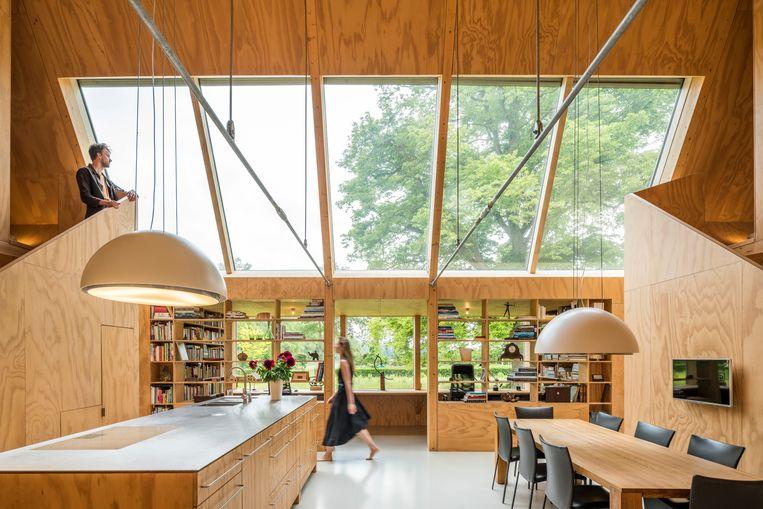 De twee theatrale trappen aan weerszijden van de leefkeuken leiden naar twee gastenkamers. In de erker is een bibliotheek en bureau ingericht.   Beeld Luc Roymans