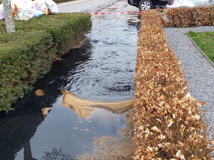 Rioolwater stroomt over straat.