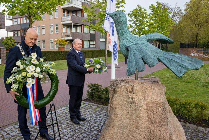 Burgemeester Wim Wouters en Roeland van Hooff leggen een krans en een bloemstuk.