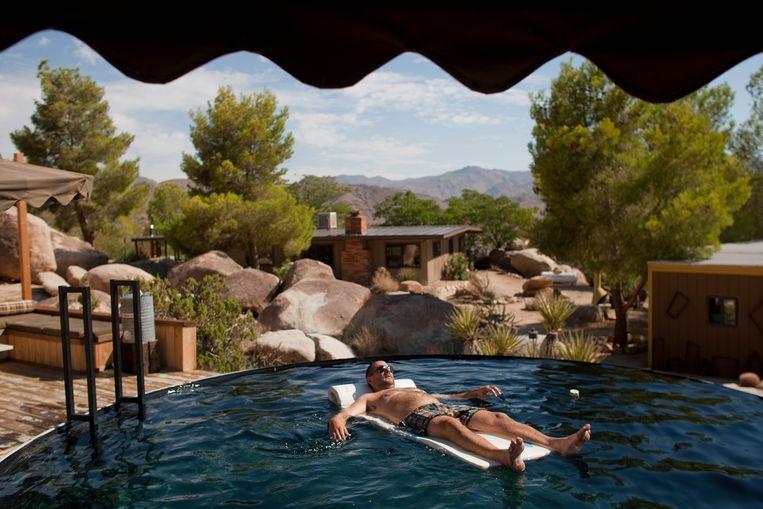 Een man geniet van het zwembad bij een bungalow in het Joshua Tree National Park, ten oosten van Los Angeles.  Beeld Los Angeles Times via Getty Imag