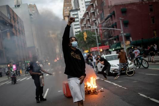 Demonstranten marcheren door de straat terwijl vuilnis op de achtergrond brandt.