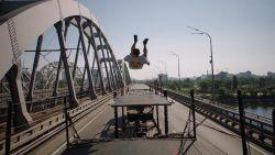 Stuntman doet zotte sprong op rijdende trucks