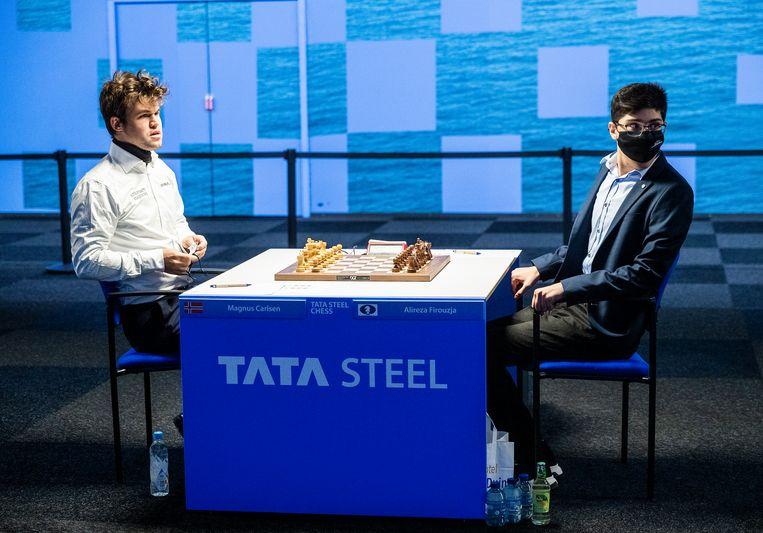 Magnus Carlsen en Alireza Firouzja zitten klaar voor hun partij. Beeld Jiri Buller