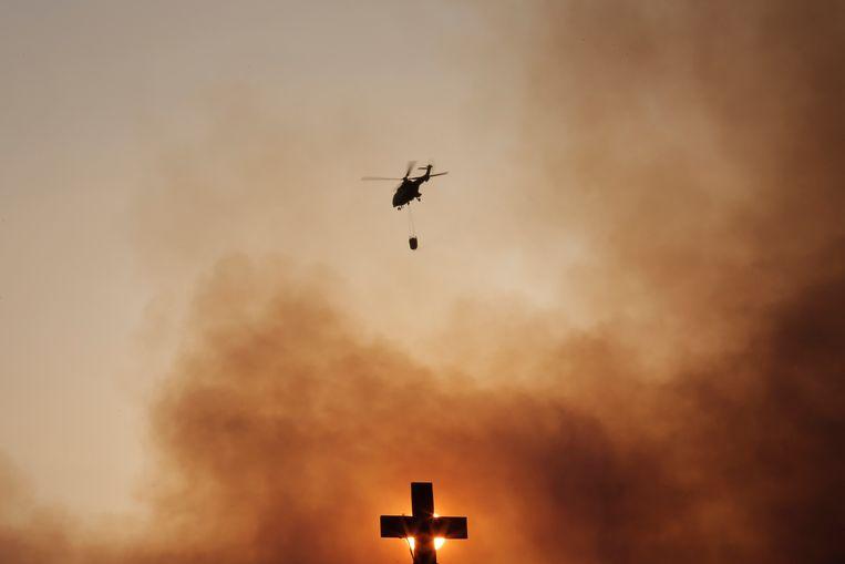 Een brandweerhelikopter dropt water op het vuur bij een bos bij Kryoneri, nabij Athene.  Beeld EPA