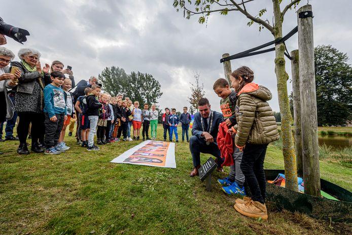 Loco-burgemeester Eugène van Mierlo markeert de vredesboom, de jongste generatie is erbij.