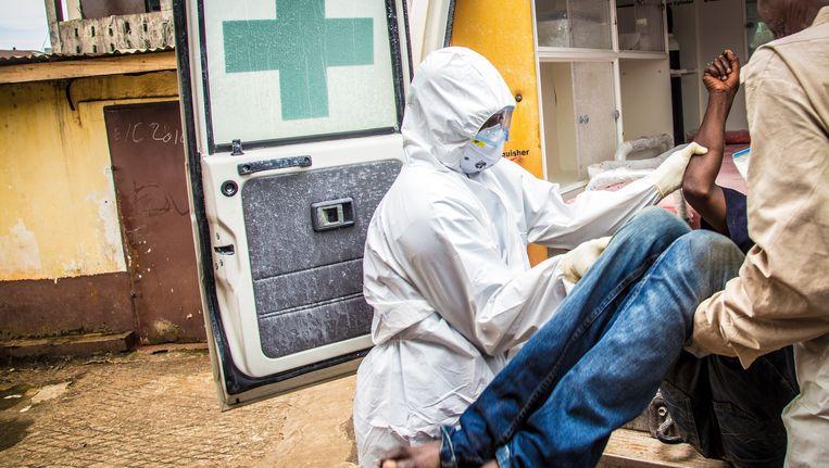 Een ebolpatiënt wordt een ambulance in Sierra Leone ingetild Beeld ap