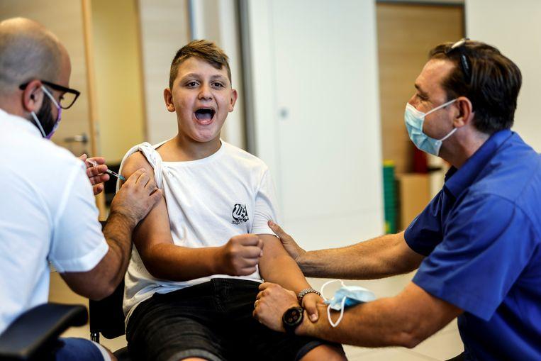 Een jongere wordt gevaccineerd tegen Covid-19. Beeld REUTERS