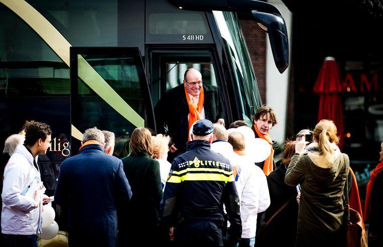 De bus arriveert in Amstelveen, Fred Teeven - met oranje sjaal - stapt uit. Beeld anp
