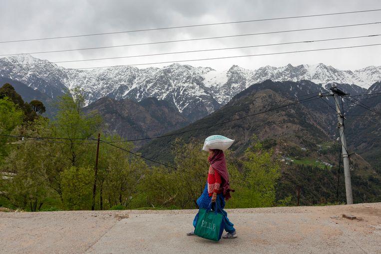 Een vrouw in India doet tijdens een onderbreking van de lockdown boodschappen. De Himalaya op de achtergrond is al decennia een gebied waar buurlanden India, China en Bhutan met elkaar overhoop liggen over de juiste landsgrenzen. Beeld AP