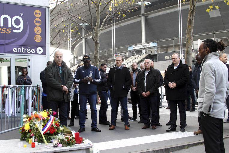 Bij het Stade de France, waar drie bommen afgingen vrijdag, wordt een minuut stilte gehouden. Beeld ap