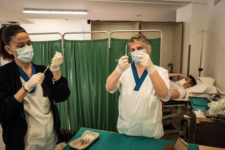 Verplegend personeel in San Marino maakt de spuiten met het Russische vaccin Spoetnik klaar. Beeld Nicola Zolin