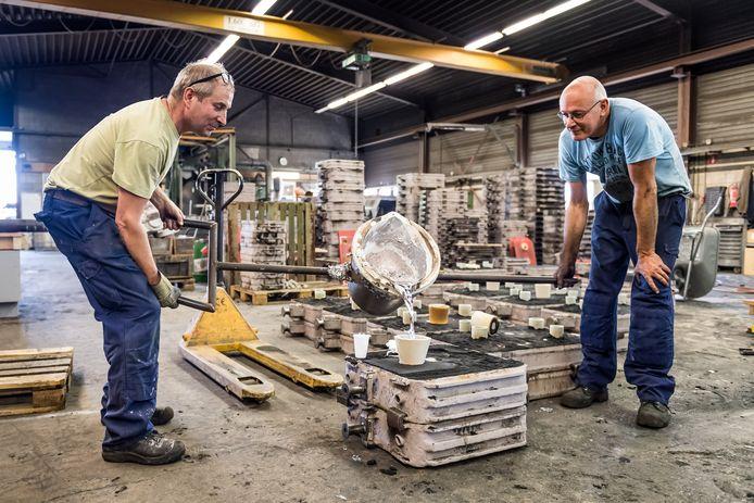 Wim Pluijgers (links) en Bertus Meijer van non-ferro gieterij Christenhusz bezig met het gieten van de zittingen van het Menthol-bankje.