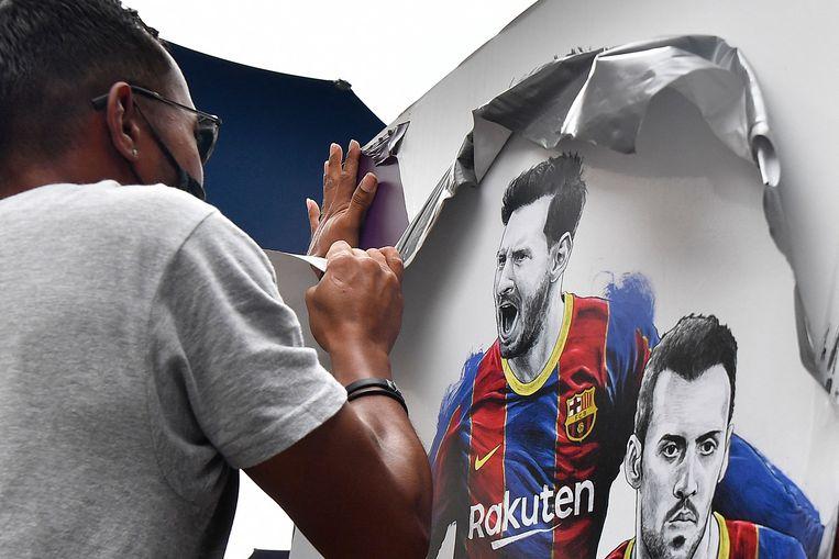 Posters met de afbeelding van Lionel Messi worden verwijderd bij het stadion van FC Barcelona.  Beeld AFP