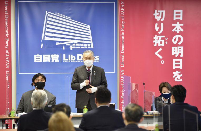 Yoshiro Mori (met wit mondkapje) tijdens een vergadering deze week ter voorbereiding van de Olympische Zomerspelen in Tokio.   Beeld EPA