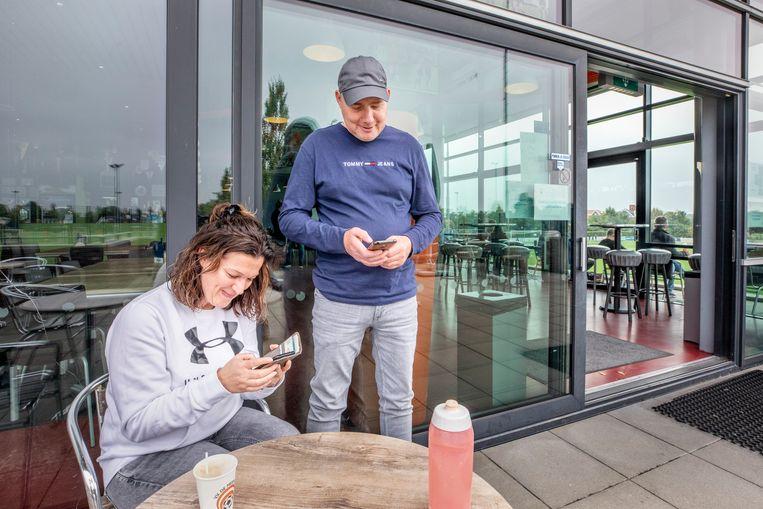 Arianne en Jan Lamoré uit Zeist proberen bij de sportkantine van VV De Meern de corona-app te downloaden: 'Hij loopt vast.' Beeld Raymond Rutting  / de Volkskrant