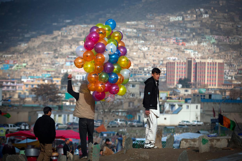 Een ballonnenverkoper bij een heiligdom dat een centrale rol speelt bij het Nowruz-festival, het Perzisch Nieuwjaar. Beeld Getty Images