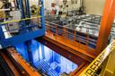 Splijtstofstaven staan in kobaltblauw licht onder water voor koeling. De kleding van het personeel verdwijnt elke dag in de eigen wasmachines.