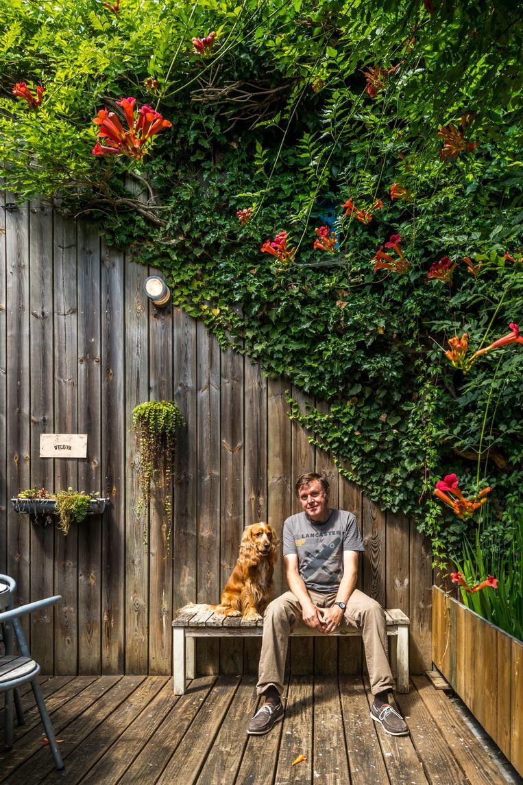 Huub Berger en zijn hond Jefke samen op het terras dat hij zelf aanlegde met deels gerecupereerde materialen.