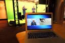 André Kuipers beantwoordt tijdens de College Tour voor een groen scherm in het Evoluon vragen van leerlingen.