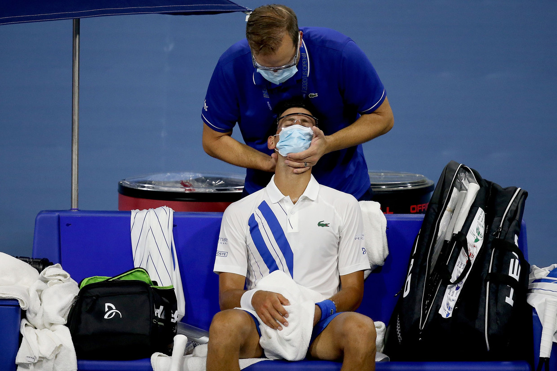 Novak Djokovic krijgt een medische behandeling tijdens de Western & Southern Open in New York. Beeld AFP
