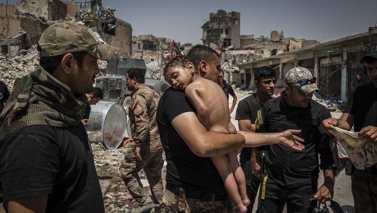 Een jongen wordt weggedragen uit voormalig IS-gebied door Iraakse militairen Beeld Ivor Prickett/The New York Times