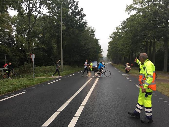 Deelnemers aan de Landgoed Twente Marathon steken de Bentheimerstraat over.