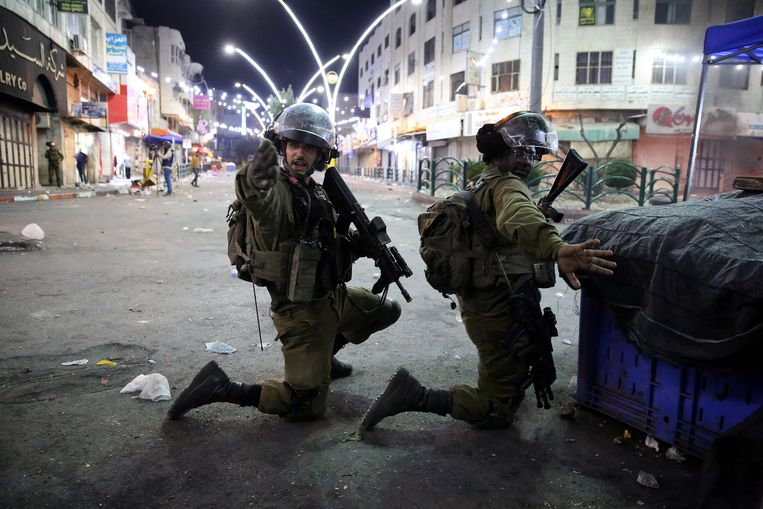 Israëlische troepen leveren slag met Palestijnse protestanten in de stad Hebron. Beeld EPA