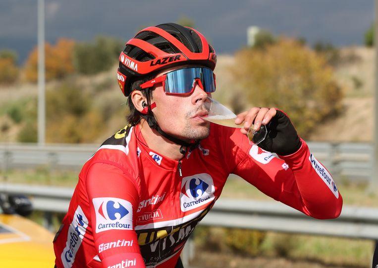 Primoz Roglic drinkt een glas champagne op de fiets. Beeld EPA