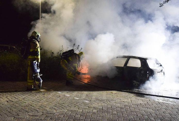De brandweer blust de auto aan de Bizetlaan in Doetinchem, die op dat moment al bijna geheel uitgebrand is.