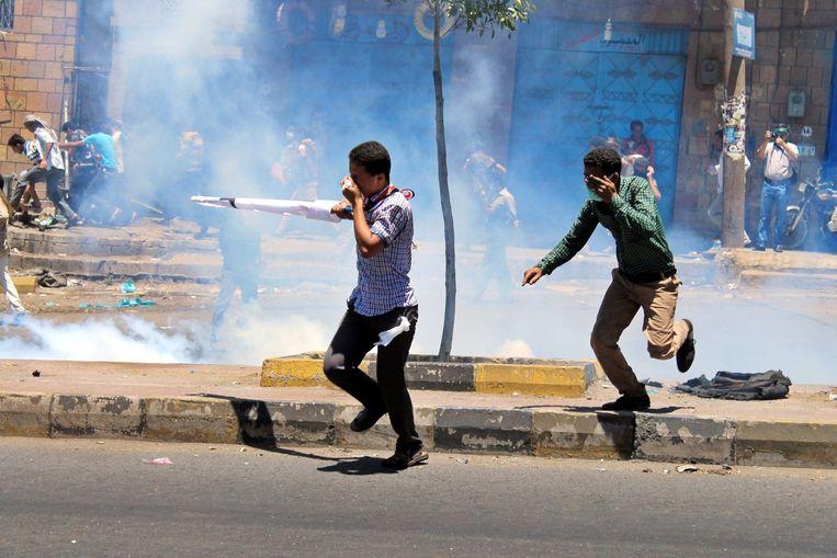Inwoners van Taiz in Jemen slaan op de vlucht voor traangas. Beeld ANP