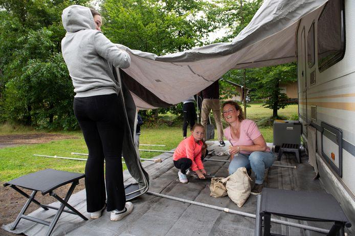 Schuilen onder de voortent terwijl de rest van de familie Pool uit Vlaardingen de kampeerplek op Het Grote Bos in Doorn in orde maakt.