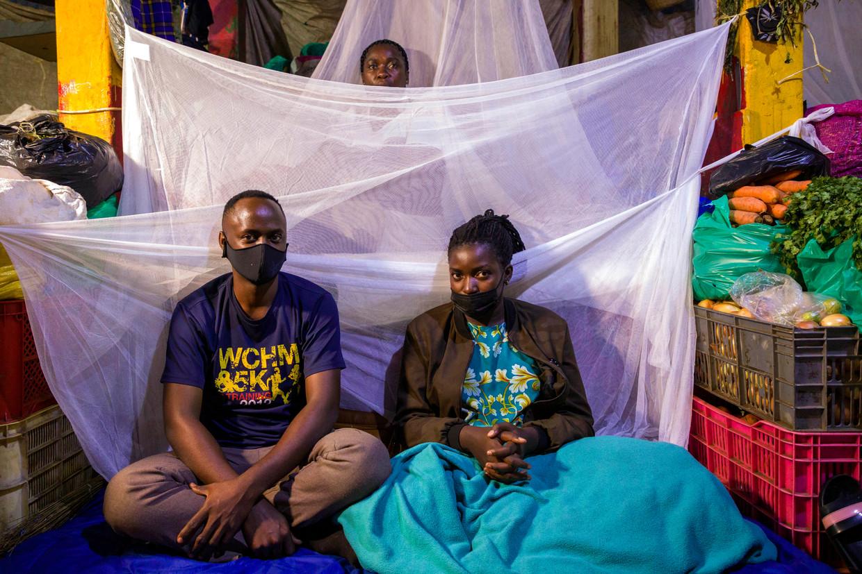 Abu Kikomeko (links), zijn zus Rebecca Nakyanzi en moeder Glades Ssebwira maken zich op om bij hun kraam op de markt van Nakasero in Kampala te gaan slapen. Vanwege nieuwe lockdownregels in Oeganda moeten marktkooplui 42dagen lang of thuis of op hun markt blijven om te voorkomen dat ze het virus verspreiden.  Beeld Katumba Badru