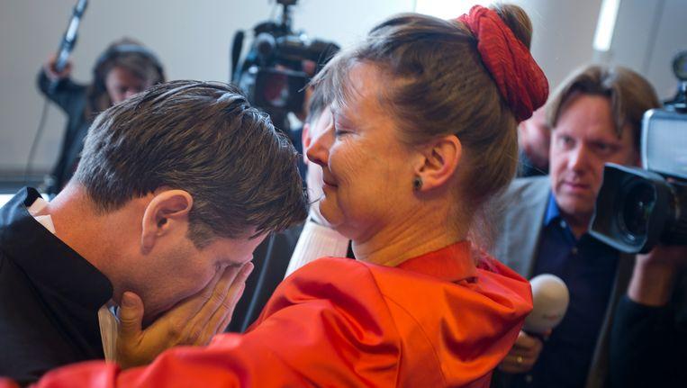 Een emotionele advocaat Roger Cox (links) krijgt een knuffel van Urganda-directeur Marjan Minnesma na de uitspraak. Beeld AP