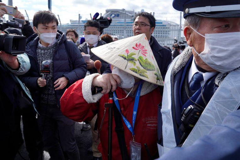 Een vrouw met een hoedje wordt belaagd door journalisten nadat ze de Diamond Princess verliet.
