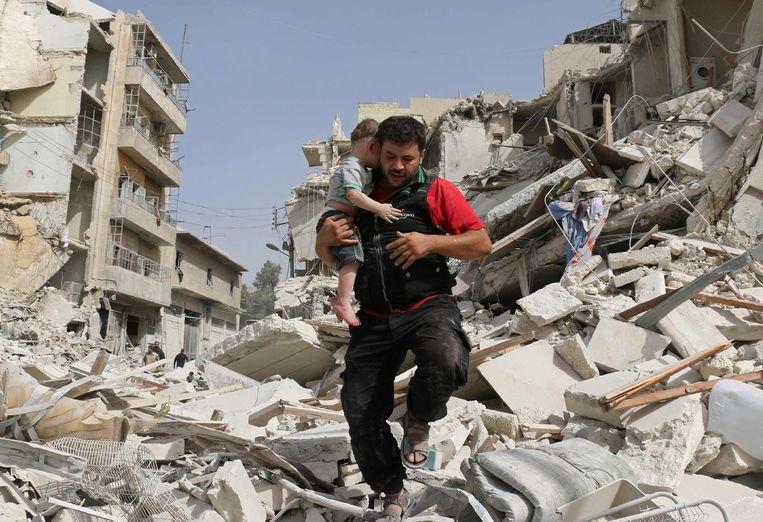 Een Syrische hulpmedewerker draagt een baby weg in de wijk Qatarji in Aleppo. Beeld afp