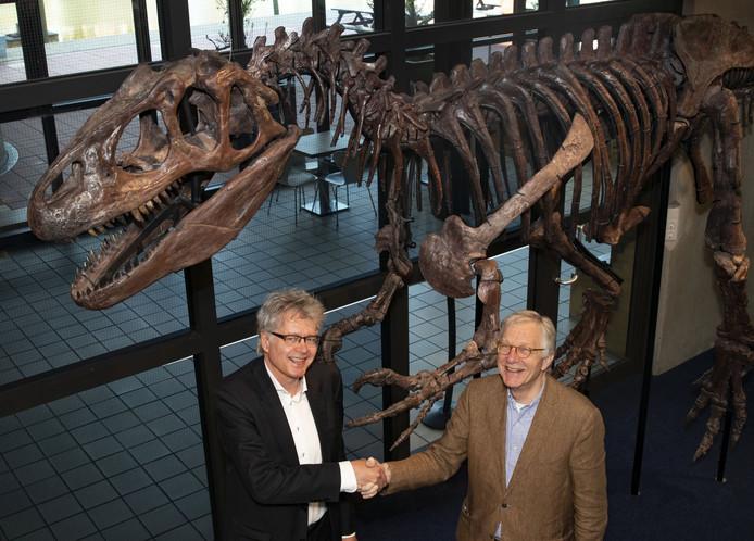 De 150 miljoen jaar oude, authentieke Allosaurus van het Museon, is weer te zien voor het publiek. Peter de Haan, directeur van het Museon (links op de foto), feliciteert Dick van der Krogt, voorzitter van de Vrienden, met de hernieuwde kennismaking met de vleeseter in de winkel.